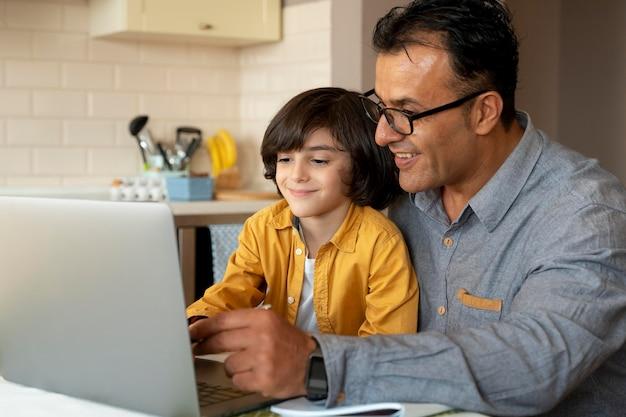 Ojciec pomaga synowi w zajęciach online