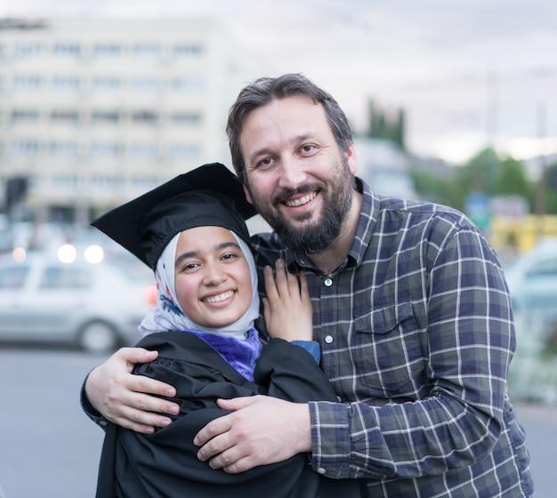 Ojciec pozdrawia córkę po ukończeniu studiów