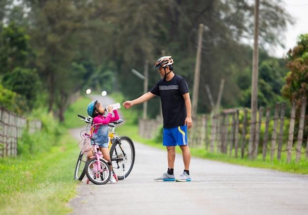 Ojciec pozwolił córce pić wodę podczas jazdy na rowerze w parku