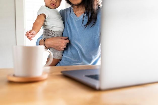 Ojciec pracujący w domu z dzieckiem