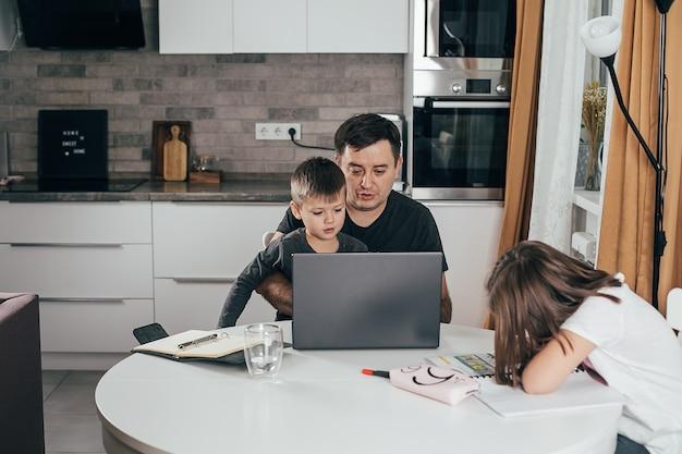 Ojciec pracujący w domu z dziećmi przy kuchennym stole