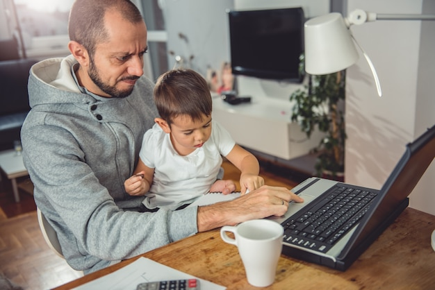Ojciec pracuje na laptopie i trzyma syna na kolanach