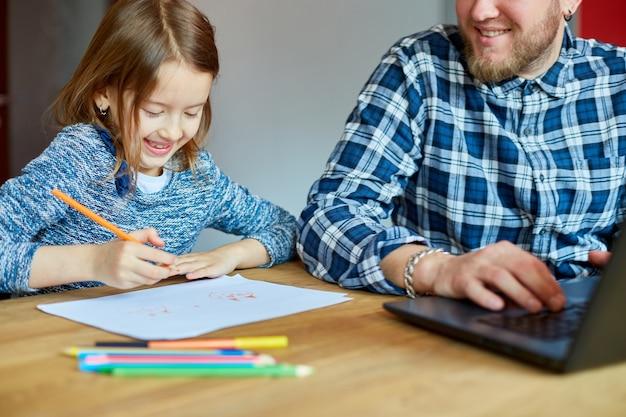 Ojciec pracuje na laptopie w swoim domowym biurze, jej córka siedzi obok niej i rysuje