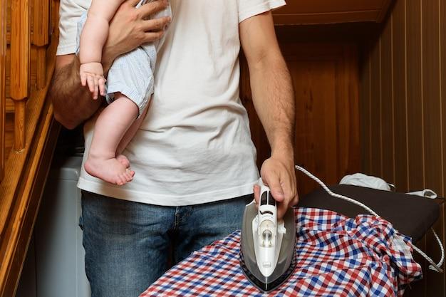 Ojciec prasuje pościel i trzyma w ramionach małe dziecko
