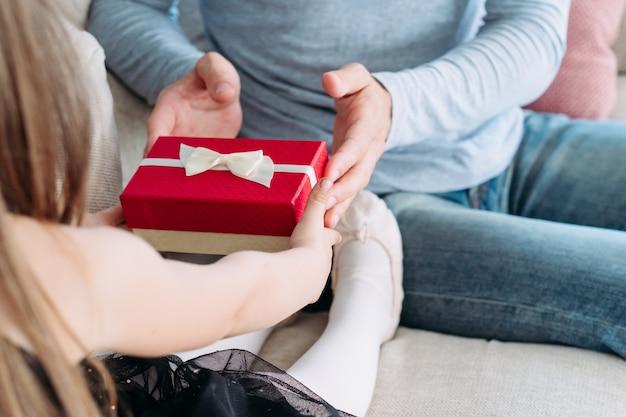 Ojciec prezentujący swoją małą córeczkę w czerwonym pudełku. szczęśliwego dzieciństwa i dobrego rodzicielstwa.