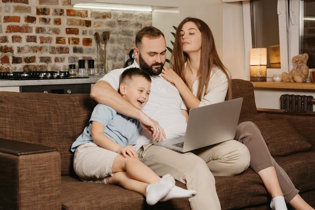 Ojciec próbuje pracować zdalnie na laptopie w pobliżu swojego uśmiechniętego syna i ciekawskiej żony w domu. wieczorem rodzina przy kanapie. tata pracuje online na komputerze między krewnymi.