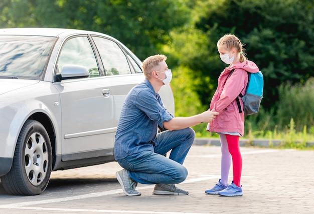 Ojciec prowadzi małą dziewczynkę z powrotem do szkoły w maskach medycznych