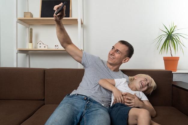 Ojciec przy selfie z synem, siedząc i robiąc miny. ojciec i syn bawią się razem.