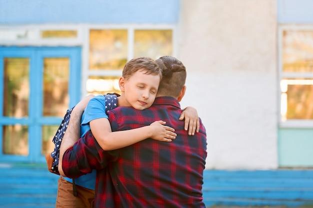 Ojciec przytula swoje dziecko przed pójściem do szkoły
