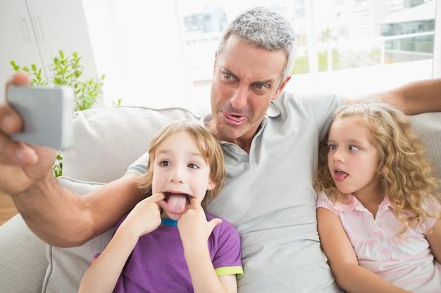 Ojciec robi twarzy podczas gdy brać selfie z dziećmi