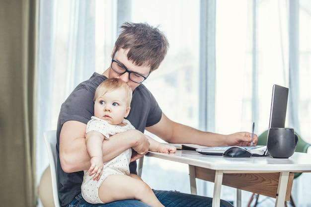 Ojciec rodziny pracuje z laptopem przez internet, a dziecko jest szczęśliwe razem w domu uśmiechnięte
