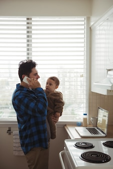 Ojciec rozmawia przez telefon komórkowy, trzymając swoje dziecko