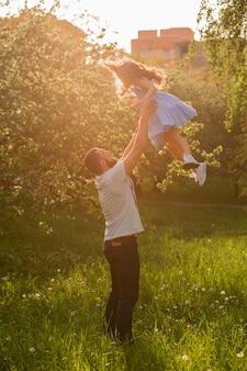 Ojciec rzuca córkę w powietrzu w słoneczny dzień
