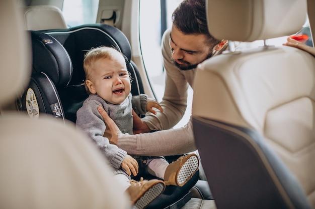 Ojciec sadza córkę w foteliku samochodowym