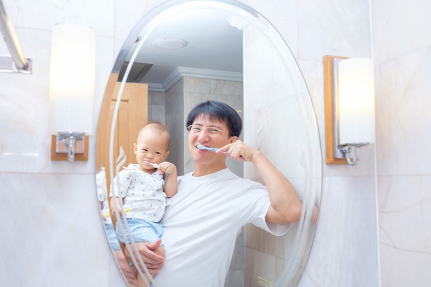 Ojciec sian uczy szczotkowanie zębów dla dzieci, śliczny azjatycki 18 miesięcy / 1-letni chłopiec myjący zęby
