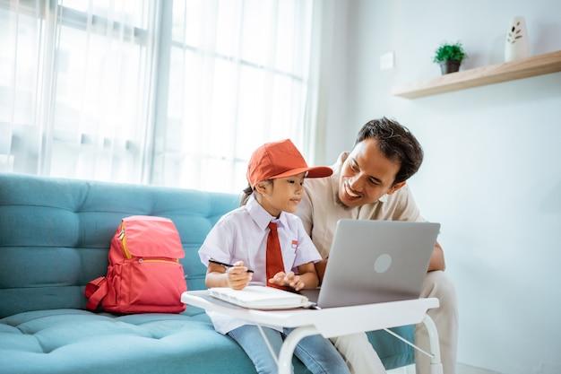 Ojciec siedzący obok córki podczas jej internetowej konferencji klasowej