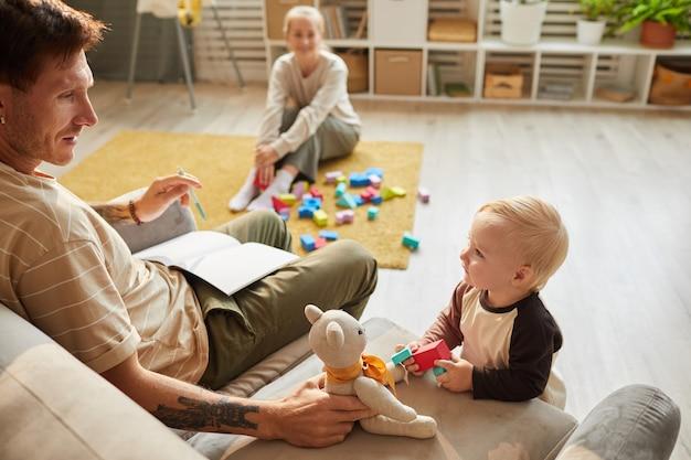 Ojciec siedzi na kanapie i bawi się z misiem razem z synkiem z matką siedzącą w pokoju