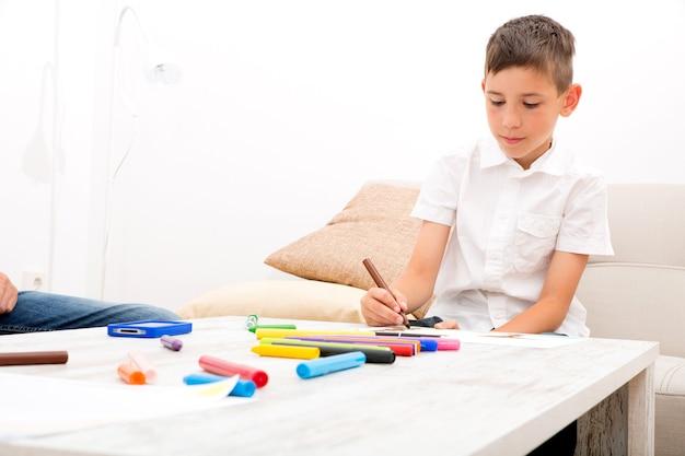 Ojciec siedzi na kanapie, podczas gdy jego syn rysuje.
