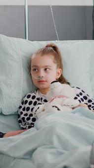 Ojciec siedzi obok chorej córki, omawiając terapię choroby, wyjaśniając leczenie farmakologiczne