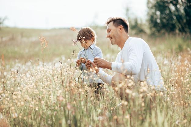Ojciec spędza czas ze swoim synkiem w lesie na trawniku z kwiatami, opowiada mu o roślinach