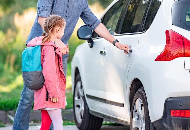 Ojciec spotyka córkę po szkole i otwiera tylne drzwi samochodu