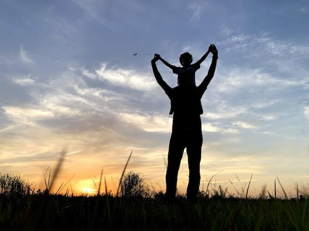 Ojciec sylwetka prowadzenie syna przeciwko niebo podczas zachodu słońca