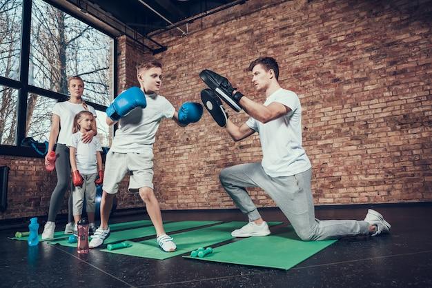 Ojciec trenuje małych bokserów na siłowni.