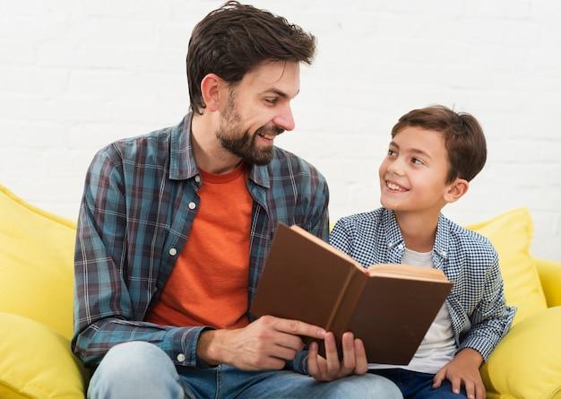Ojciec trzyma książkę i patrzeje jego syna