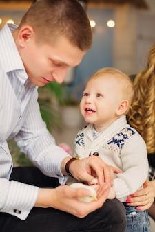 Ojciec trzyma małego kurczaka i patrzy na niego mały syn w pięknym ubraniu