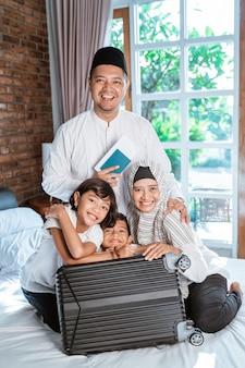 Ojciec trzyma paszport, gdy członkowie rodziny przygotowują walizkę do noszenia, gdy mudik