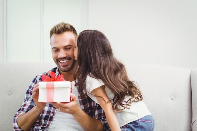 Ojciec trzyma pudełko, podczas gdy jego córka go całuje