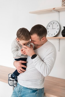 Ojciec trzyma swoje dziecko i kubek w kuchni