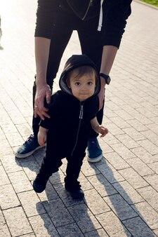 Ojciec trzyma syna spacerującego po parku na placu w soczi