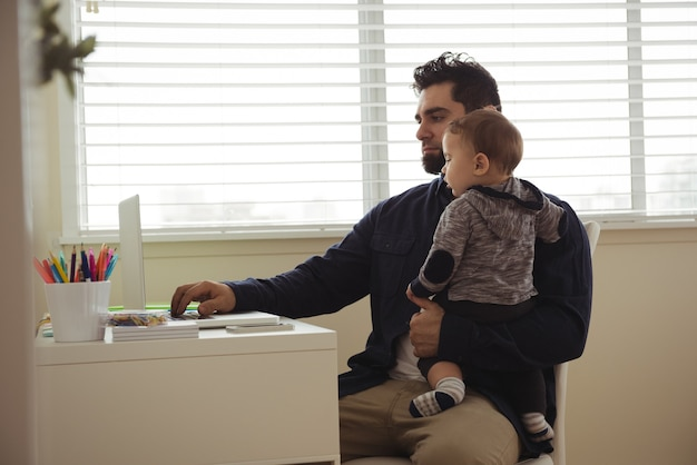 Ojciec trzymając dziecko podczas korzystania z laptopa przy biurku