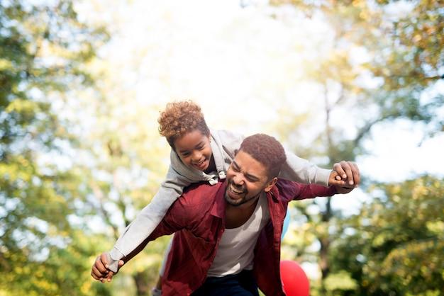 Ojciec trzymający córkę na ramionach i śmiejący się