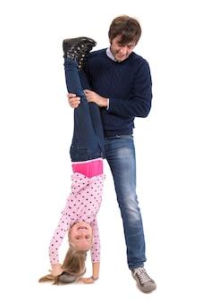 Ojciec trzymający swoją uśmiechniętą córkę do góry nogami na białej ścianie
