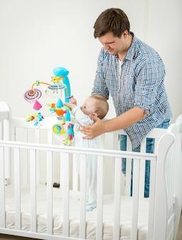 Ojciec trzymający swojego 9-miesięcznego synka w łóżeczku
