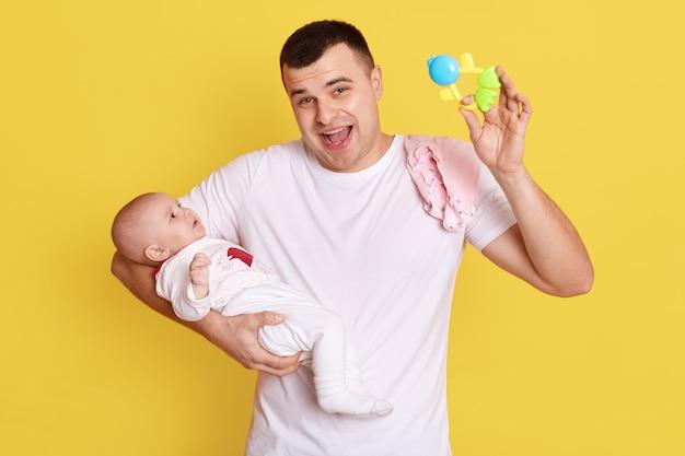 Ojciec trzymający zabawkę worek fasoli i animujący dziecko w dłoni, pozujący odizolowany na żółtej ścianie, szczęśliwy wrzeszczący przystojny tata ubrany w białą koszulkę dorywczo bawiący się z niemowlęciem.