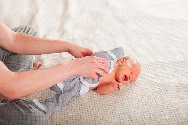 Ojciec ubiera noworodka w sypialni. odzież dziecięca podkoszulki i suwaki na dziecko bliska i miejsca kopiowania.