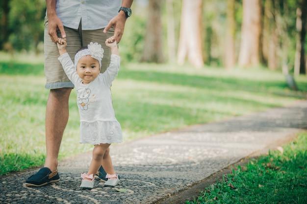 Ojciec uczy dziecko chodzić w parku