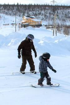 Ojciec uczy dziecko jeździć na snowboardzie. zimowa zabawa w mroźny, śnieżny dzień. wspólne rodzinne wakacje