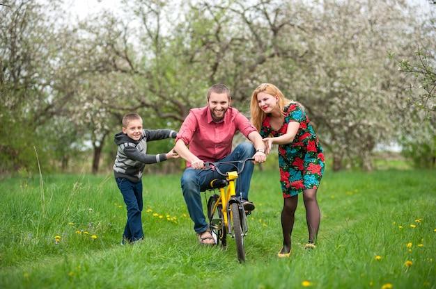 Ojciec uczy syna, aby jeździć na rowerze na swoim przykładzie
