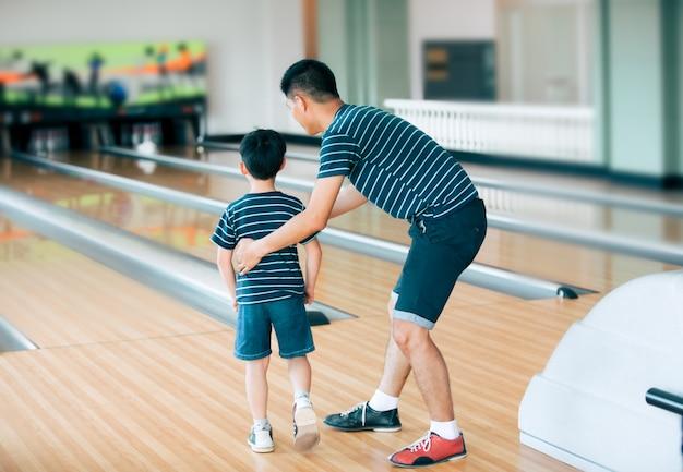 Ojciec uczy syna do gry w kręgle w kręgielni