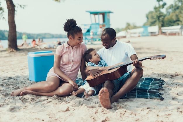 Ojciec uczy syna gra na gitarze