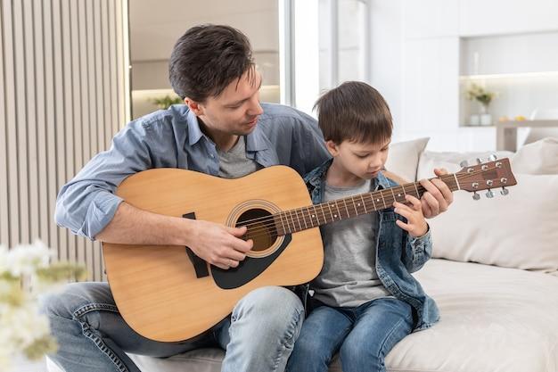Ojciec uczy syna grać na gitarze