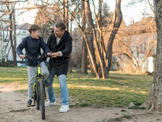 Ojciec uczy syna, jak jeździć na rowerze długi widok