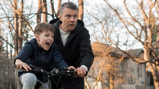 Ojciec uczy syna, jak jeździć na rowerze