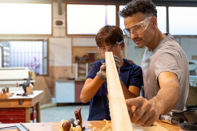 Ojciec uczy syna, jak pracować z drewnem w stolarce.