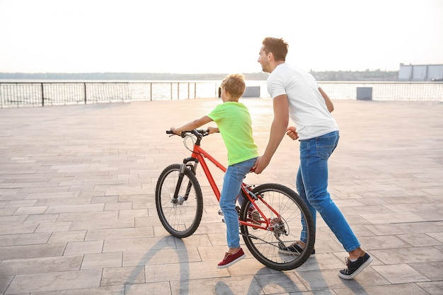 Ojciec uczy syna jeździć na rowerze na świeżym powietrzu