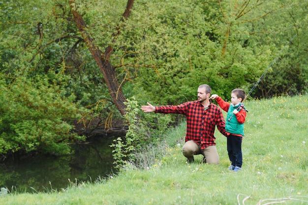 Ojciec uczy syna łowić ryby na rzece w letnim słońcu